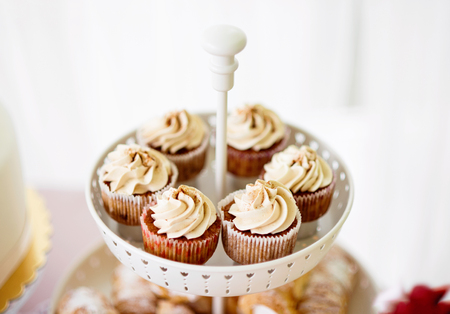 close shot: Close up, cupcakes with vanilla cream in white cakestand. Studio shot.