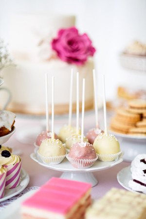 Table with white and pink cake pops on cakestand and various cakes. Candy bar. Stock Photo
