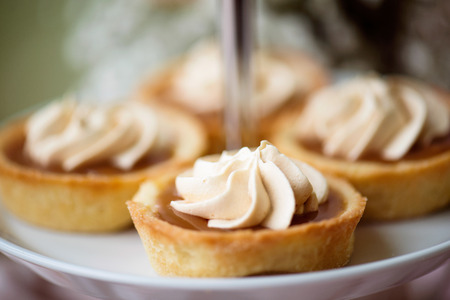 cakestand: Close up, tarts filled with jam decorated with vanilla cream laid on cakestand. Studio shot.