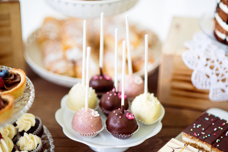 cakestand: Table with white, pink and chocolate cake pops on a plate, tarts and cupcakes on cakestand. Candy bar.