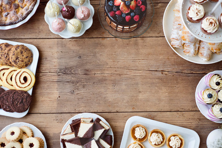 Table with cake, pie, cupcakes, tarts and cakepops. Frame composition. Studio shot on brown wooden background. Copy space. Flat lay. Stock Photo