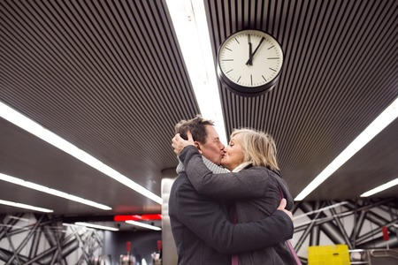 good bye: Beautiful senior couple standing at the underground platform, hugging and kissing. Welcoming or saying good bye. Five past twelve.