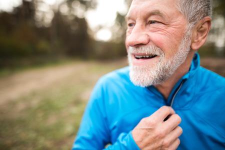 Close-up van senior runner in de natuur. Man in blauw sweatshirt, rusten, glimlachend.