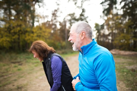 couple nature: Beautiful active senior runners outside in sunny autumn forest