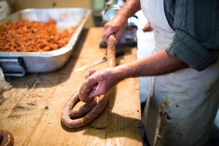cocina antigua: Hombre irreconocible hacer embutidos de forma artesanal mediante relleno de salchicha. salchicha casera. Foto de archivo