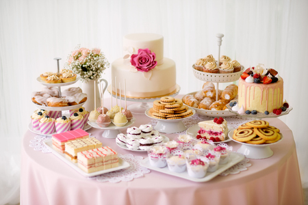 Tabel met tal van taarten, cupcakes, koekjes en cakepops. Studio-opname.