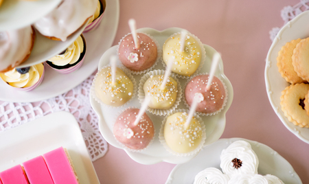 cakestand: Table with white and pink cake pops on cakestand and various cakes. Candy bar. Stock Photo