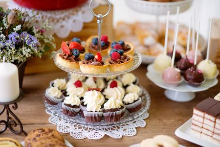 Bruine houten tafel met verschillende koekjes, taarten, cakes, cupcakes en cakepops. Studio-opname. Stockfoto