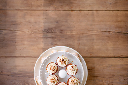 cakestand: Close up, cupcakes with vanilla cream in white cakestand. Copy space. Studio shot on brown wooden background. Stock Photo