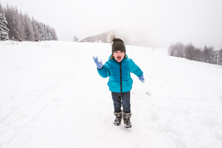 boy ball: Cute little boy in blue jacket and hat playing outside in snow in winter nature, throwing snow ball, shouting