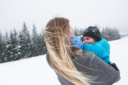 view to outside: Beautiful young mother outside having fun with her son, playing in the snow. Foggy white winter nature. Rear view. Stock Photo