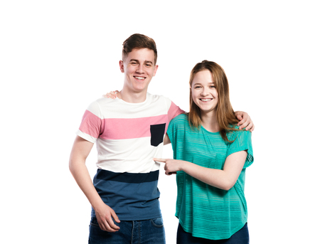 poking: Teenage boy and girl with arms around each other, smiling. Young woman in green t-shirt poking man in striped t-shirt. Studio shot on white background, isolated. Stock Photo