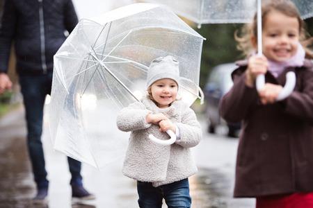 우산 아래 두 딸과 인식 할 수없는 아버지. 비오는 날에 거리에서 걷기. 스톡 콘텐츠