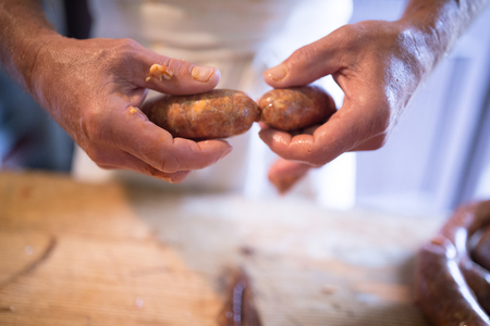 Hands of unrecognizable man making sausages the traditional way at home. Close up.