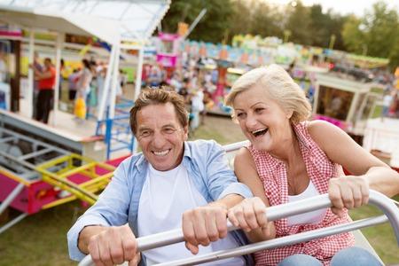 Senior couple having fun on a ride in amusement park. Summer vacation. Standard-Bild
