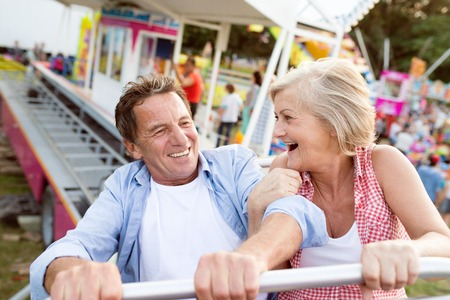 amusement park ride: Senior couple having fun on a ride in amusement park. Summer vacation. Stock Photo