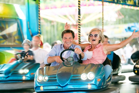 Senior couple having a ride in the bumper car at the fun fair Stock Photo