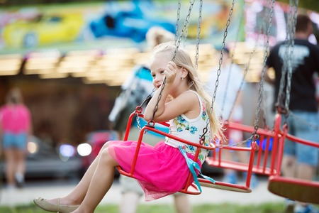 chain swing ride: Cute little girl enjoing time at fun fair, chain swing ride, amusement park in summer Stock Photo