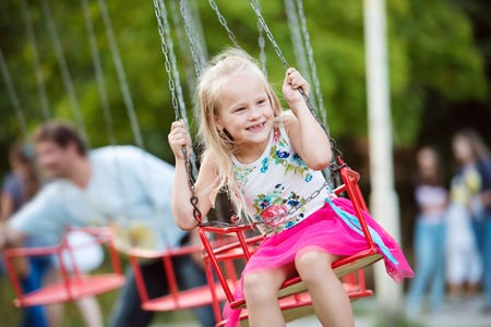 enjoing: Cute little girl enjoing time at fun fair, chain swing ride, amusement park in summer Stock Photo
