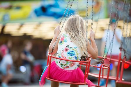 chain swing ride: Cute little girl enjoing time at fun fair, chain swing ride, amusement park in summer. Rear view.