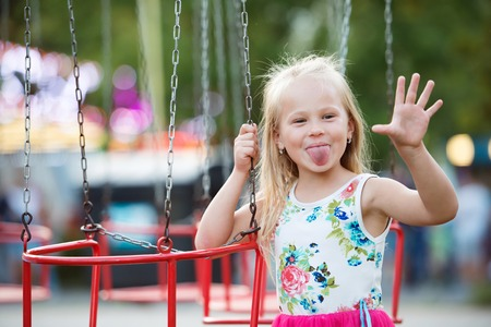 Cute little girl enjoing time at fun fair, chain swing ride, amusement park in summer Stock Photo