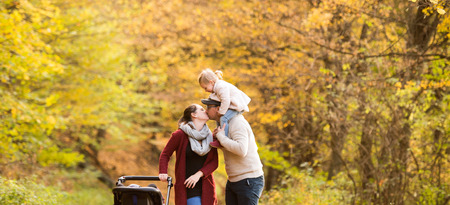 Beautiful young family on a walk in forest. Father giving his daughter piggyback and kissing mother with her son in pushchair outside in colorful autumn nature. Stock Photo
