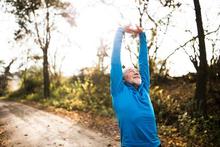 Senior loper in zonnige herfst de natuur doen stretching. Man met grijze baard en snor dragen blauwe sweater oefenen.