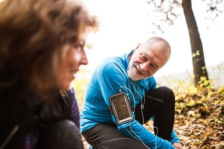 la escucha activa: Corredores mayores en la naturaleza, atar cordones. Hombre con teléfono inteligente y auriculares. Escuchando música o usando una aplicación de fitness. Uso de la aplicación de teléfono para el seguimiento de la pérdida de peso progreso, meta de carrera o un resumen de su carrera.