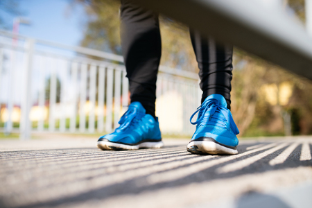 Legs of unrecognizable runner standing on concrete path wearing blue sports shoes, close up.