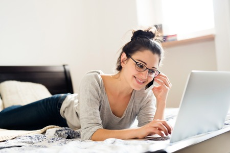 homeoffice: Beautiful young woman wearing eyeglasses lying on bed, working on notebook, holding a smart phone, making a phone call, home office.