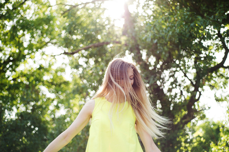 Beautiful young woman with long blowing blonde hair in neon yellow tank top. Sunny summer day.