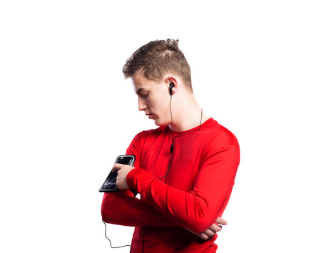 background settings: Teenage boy in red sports sweatshirt, adjusting settings on smart phone in his armband. Handsome young sportsman wearing earphones, listening music. Studio shot on white background, isolated.