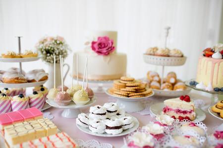Tabel met tal van taarten, cupcakes, koekjes en cakepops. Studio-opname. Stockfoto - 65740394