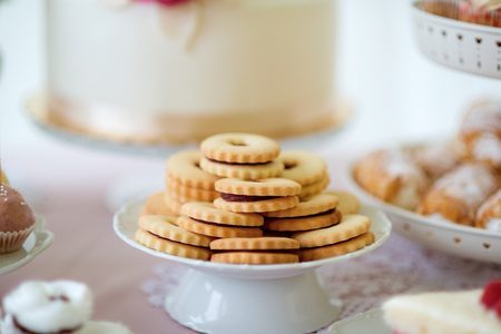 cakestand: Close up, sandwich cookies filled with jam on ceramic cakestand. Studio shot.