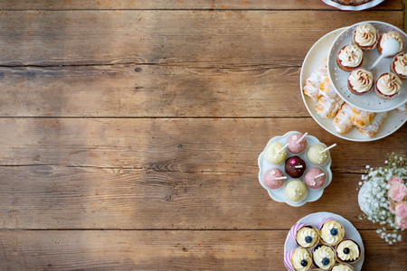 Table with cupcakes, cake pops, horn pastries and bouquet of roses in jar. Studio shot on brown wooden background. Copy space. Flat lay. Foto de archivo