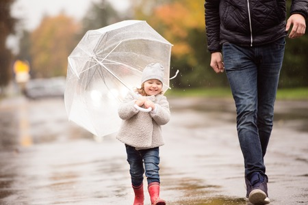 Unrecognizable young father with cute little daughter under the umbrella. Walking in the street on a rainy day.
