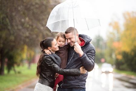 Mooie jonge familie met dochter onder de paraplu, knuffelen. Lopend in de straat op een regenachtige dag.