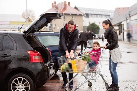 若い親は車の後部へのショッピング カートからアンロード食料品。トロリーに座っている 2 つの小さな娘。秋の雨の日。