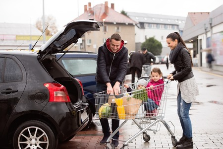 Young parents unloading groceries from shopping cart to the back of the car. Two little daughters sitting in a trolley. Autumn rainy day.