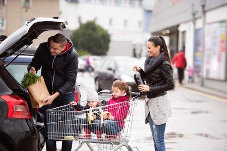 Jonge ouders lossen boodschappen van bestelling tot de achterkant van de auto. Twee kleine dochters zitten in een trolley, eten babanas. Herfst regenachtige dag. Stockfoto - 65740210