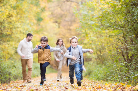 walk in: Beautiful young family on a walk in forest. Mother and father with their three sons in warm clothes outside in colorful autumn nature. Stock Photo