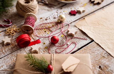 Wrapping of Christmas presents. Various objects laid on table. Studio shot, wooden background.