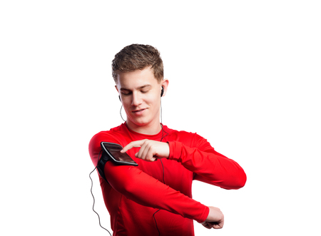 Teenage boy in red sports sweatshirt, adjusting settings on smart phone in his armband. Handsome young sportsman wearing earphones, listening music. Studio shot on white background, isolated.