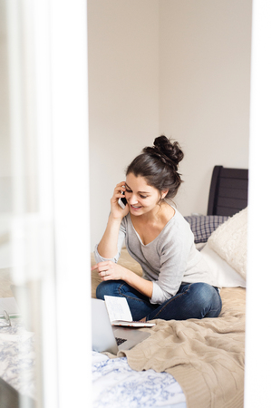 homeoffice: Beautiful young woman wearing eyeglasses sitting on bed, notebook next to her, holding smart phone, making a phone call, home office.