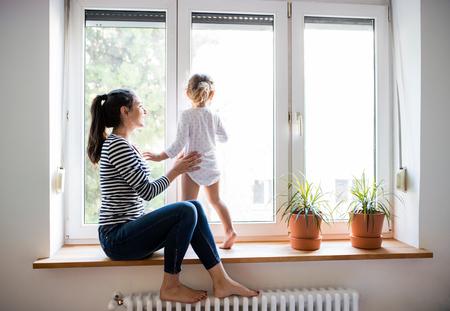 Schöne junge Mutter auf Fensterbrett sitzt mit ihrem niedlichen kleinen Tochter Blick aus Fenster