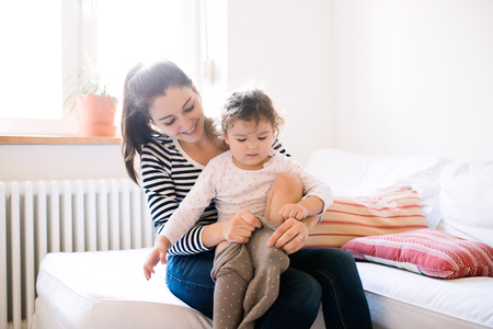 niños vistiendose: Beautiful young mother dressing her cute little daughter in the morning on a couch in living room Foto de archivo