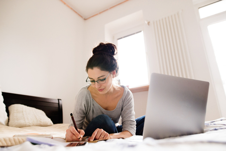 homeoffice: Beautiful young woman sitting on bed, working on laptop, writing something into her notebook, home office. Stock Photo