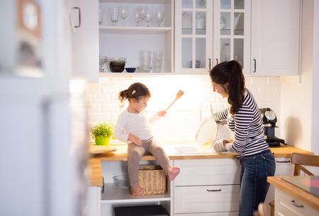 Bella giovane madre con la sua piccola figlia sveglia in cucina, la cottura della pasta insieme