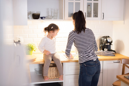back: Beautiful young mother with her cute little daughter in the kitchen, cooking pasta together