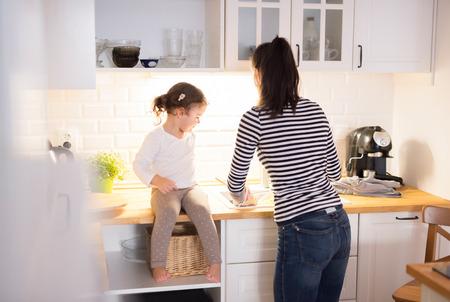 Mooie jonge moeder met haar schattige kleine dochter in de keuken, samen koken pasta